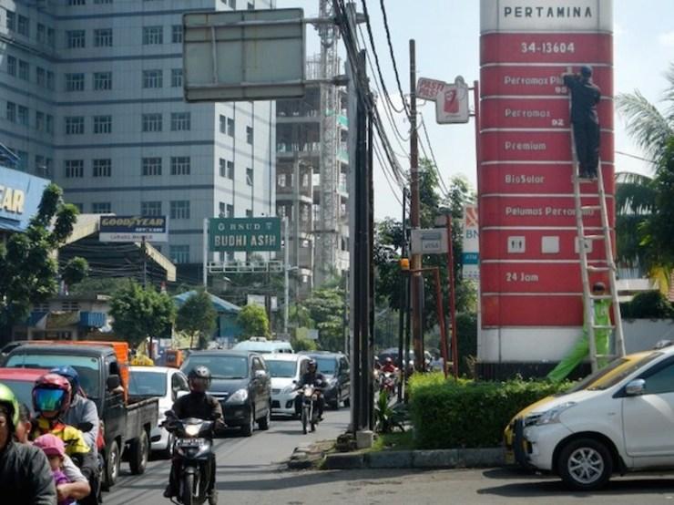 Petugas SPBU mengganti harga BBM di Jakarta. Dengan harga minyak dunia turun, pemerintah Indonesia bisa mengakomodir harga BBM disesuaikan dengan harga pasar internasional. Foto oleh Bay Ismoyo/AFP